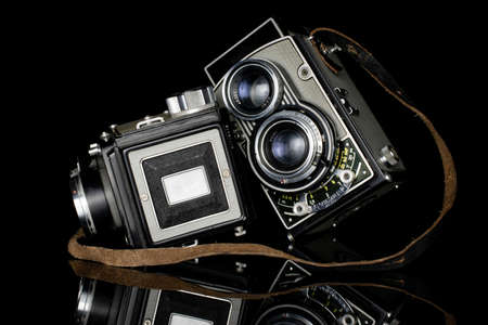Group of two whole leaning vintage camera isolated on black glass Editorial