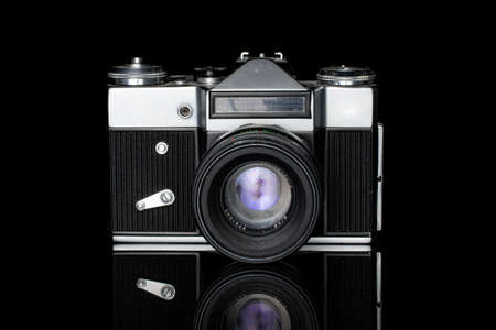 One whole old vintage camera silver black isolated on black glass Editorial