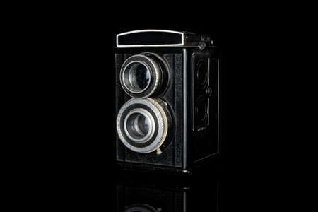 One whole vintage camera two lens isolated on black glass Editorial