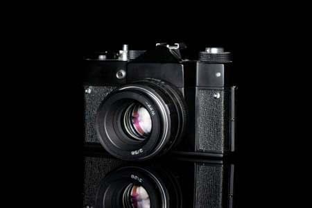 One whole black vintage camera isolated on black glass
