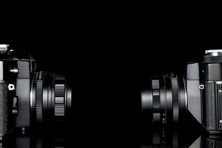 Group of two whole dark vintage camera isolated on black glass