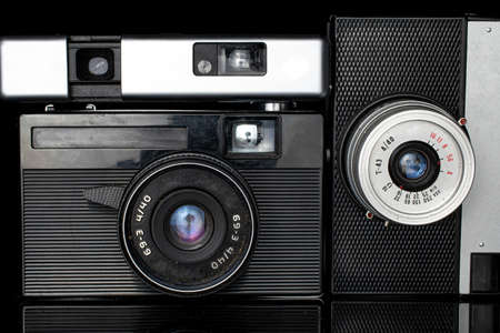 Group of three whole vintage camera closeup isolated on black glass