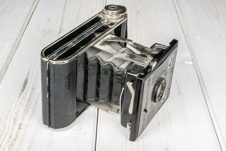 One whole opened vintage camera on white wood Editorial