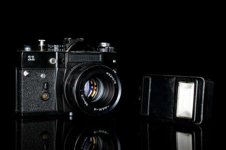 One whole camera with flash isolated on black glass Editorial