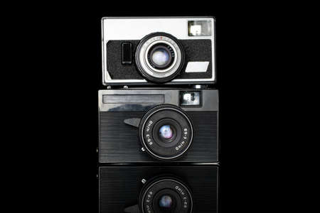 Group of two whole old vintage camera isolated on black glass