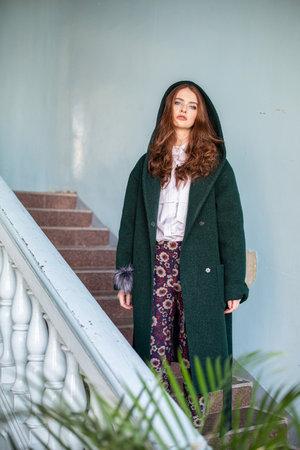 Girl in green coat standing on stairs Reklamní fotografie