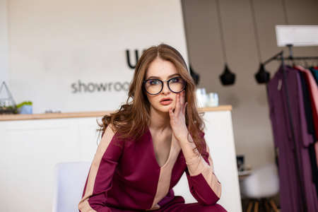 Girl in purple clothes with glasses sitting indoor Reklamní fotografie