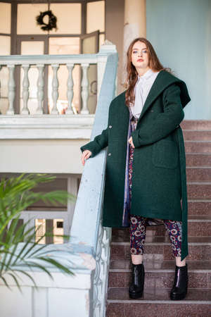 Nice girl in green coat on the stairs
