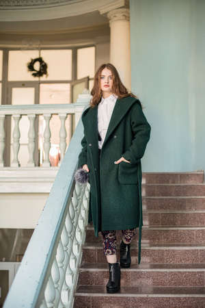 Nice girl in green coat on the stairs on the stairs