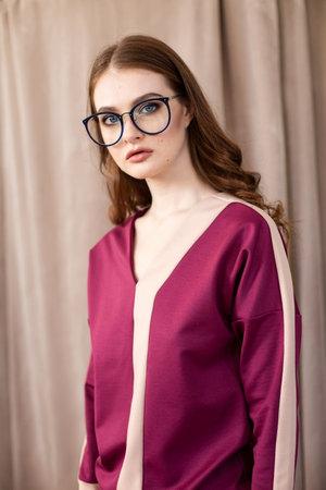 Girl in purple clothes hands behind the head portrait Reklamní fotografie