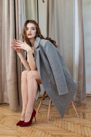 Girl in grey coat in black sitting curtains behind