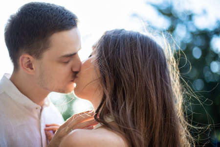 Kissing young white girl and boy portrait outside