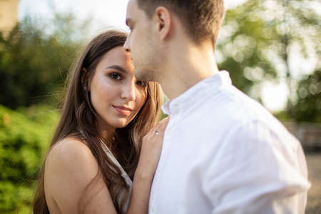 Young white couple in park european man and dark long hair woman Imagens