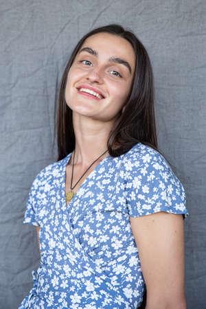 White european girl isolated on dark grey in blue dress Standard-Bild