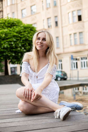 Sitting white european young model with a blonde hair on the city street