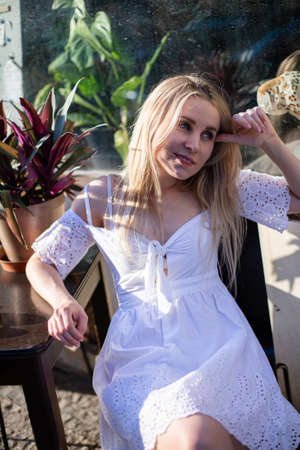 Young european white model with a blonde hair near plants