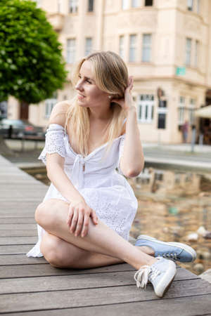 White european young model with a blonde hair on the city street touching her hair and sitting