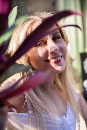 Romantic blond hair european white model with a plant Standard-Bild