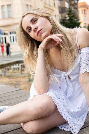 White european young model with a blonde hair sitting with hand near the face on the city street Standard-Bild