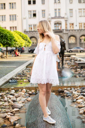White european young model with a blonde hair on the city street in white dress