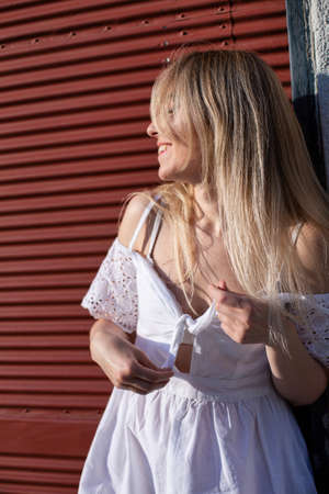 Smiling european young white model with a blonde hair near the wall Standard-Bild