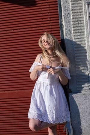 White european model with a blonde hair near the wall in white dress Standard-Bild