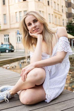 Smiling white european young model with a blonde hair sitting on the city street Standard-Bild