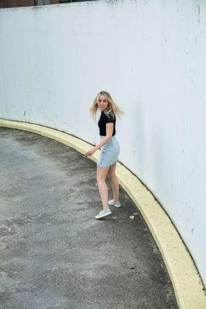 Young european white woman in skirt near city concrete walls