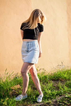 White young woman in skirt with blond hair near yellow wall and green grass