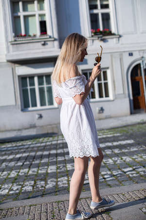 White european model with a blonde hair on the city street in white dress