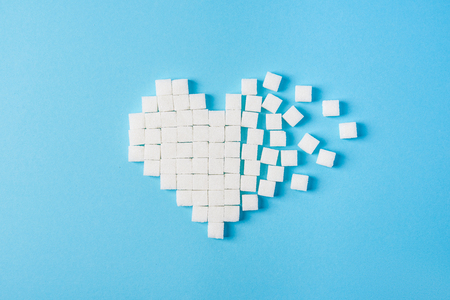 Heart made of sugar cubes on a blue background Фото со стока - 107624213