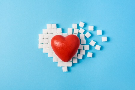 big red heart on broken heart made of sugar cubes on a blue background. World diabetes day, November 14