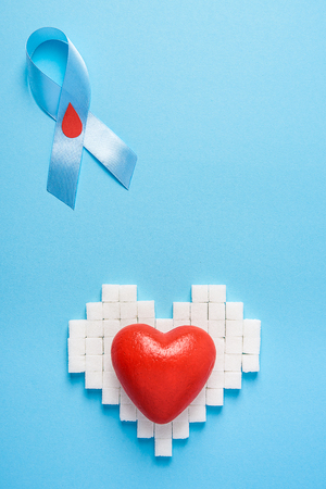 the blue ribbon awareness with red blood drop and red heart on a heart made of sugar cubes on a blue background, world diabetes day