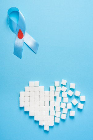 the blue ribbon awareness with red blood drop and broken heart made of sugar cubes on a blue background, world diabetes day