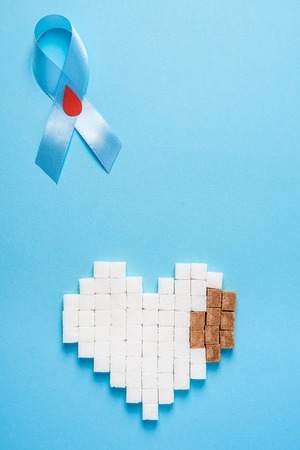 the blue ribbon awareness with red blood drop and heart made of white and brown sugar cubes on a blue background, world diabetes day