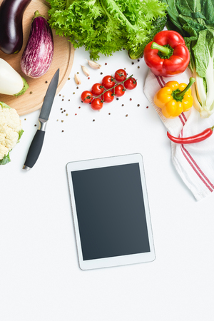 digital tablet, knife, cutting board, herbs and vegetables isolated on white background. Copy space. Healthy eating background. Food photography. Top view Stock Photo