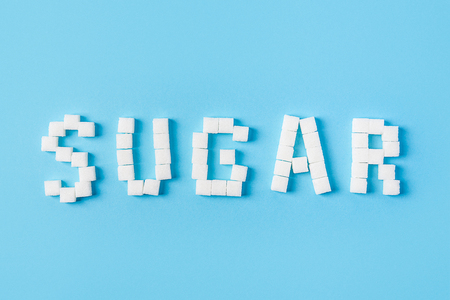 sugar inscription made of sugar cubes isolated on trendy blue background. Top view. World diabetes day