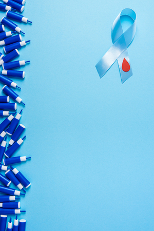 blue ribbon awareness with red blood drop and line of lancets on a blue background. World diabetes day,14 november. Copy space. Top view