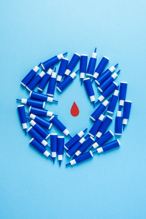 red blood drop in circle of lancets on a blue background. World diabetes day,14 november. Copy space. Top view Stock Photo