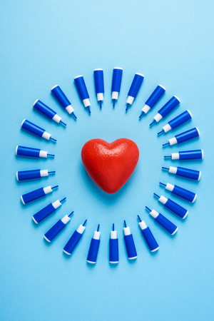 big red heart in circle of lancets on a blue background. World diabetes day,14 november. Copy space. Top view