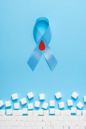 the blue ribbon awareness with red blood drop and ruiden wall made of white sugar cubes on a blue background, world diabetes day