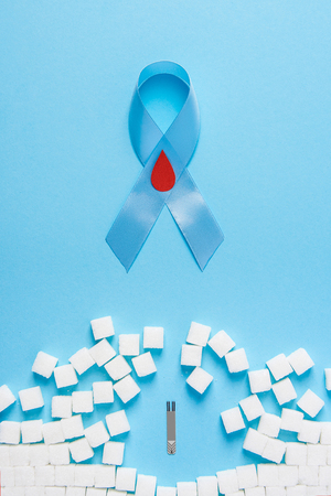 the blue ribbon awareness with red blood drop and wall made of white sugar cubes ruined by Blood Glucose Test Strips on a blue background, world diabetes day