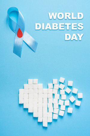 inscription world diabetes day and blue ribbon awareness with red blood drop and broken heart made of sugar cubes on a blue background. Top view. Copy space