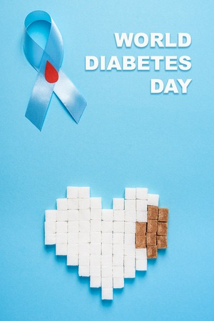 inscription world diabetes day and blue ribbon awareness with red blood drop and broken heart made of white and brown sugar cubes on a blue background. Top view. Copy space