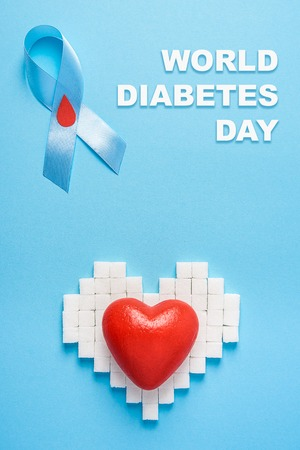inscription world diabetes day and blue ribbon awareness with red blood drop and red heart on a heart made of sugar cubes on a blue background. Top view. Copy space