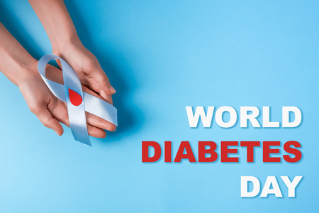 inscription world diabetes day and blue ribbon awareness with red blood drop in woman hands isolated on a blue background. World diabetes day,14 november. Copy space. Top view