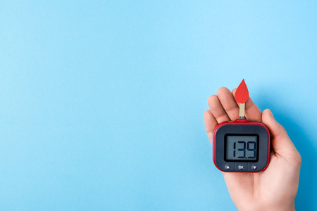 red blood drop with Blood glucose test strips and Glucose meter in man hand on blue background, world diabetes day. Copy space. Top view Stock Photo