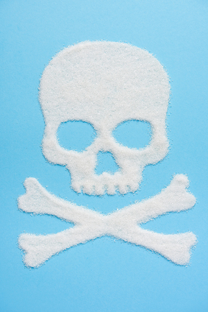 The skull made of sugar on blue blue background. Diabetes concept. Sugar Kills. Suggesting dieting concept. Unhealthy white sugar concept. Copy space. Space for text. Stock Photo