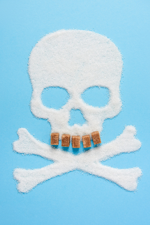 The skull made of sugar with teeth made of brown sugar cubes on blue blue background. Diabetes concept. Sugar Kills. Dieting concept. Unhealthy white sugar concept. Copy space. Space for text.