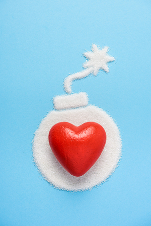 Big red heart on the bomb made of sugar on blue blue background. Diabetes concept. Sugar Kills. Suggesting dieting concept. Unhealthy white sugar concept. Copy space. Space for text. Stock Photo